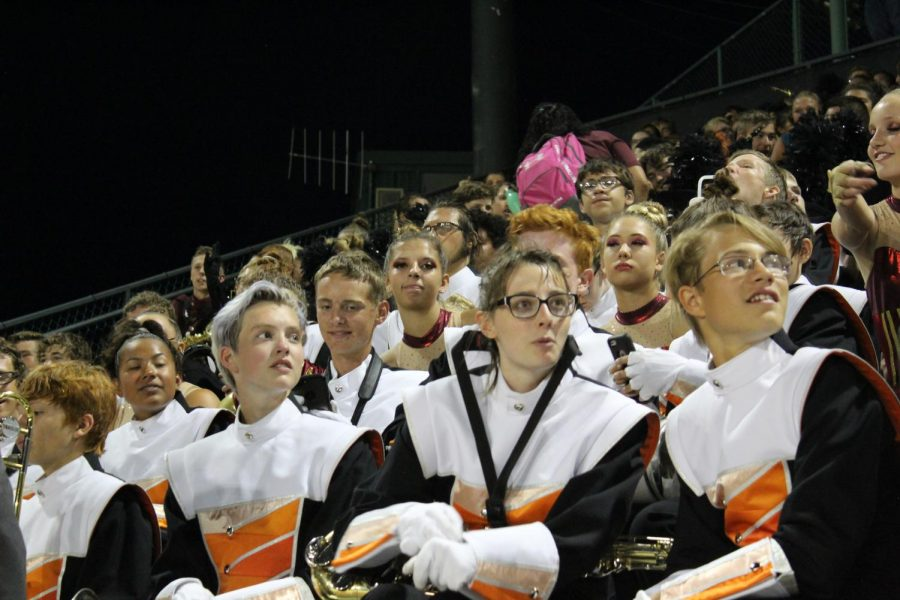 GJHS marching band sits in the stands observing and cheering on other performances.