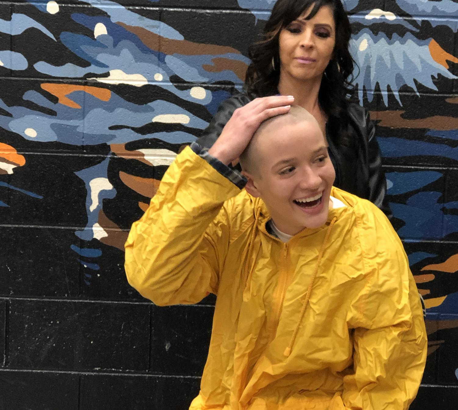 Kristin Cook, sophomore, touches her newly shaven head in excitement and surprise. Last Tuesday eight students shaved their heads to support the Leukemia and Lymphoma Society, LLS.